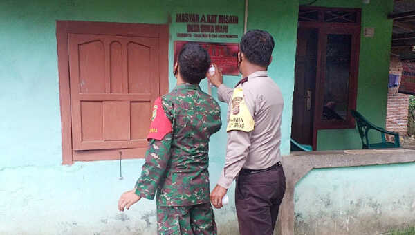 Babinsa dan Bhabinkamtibmas memasang stiker PKH di dinding rumah warga Desa Suka Maju