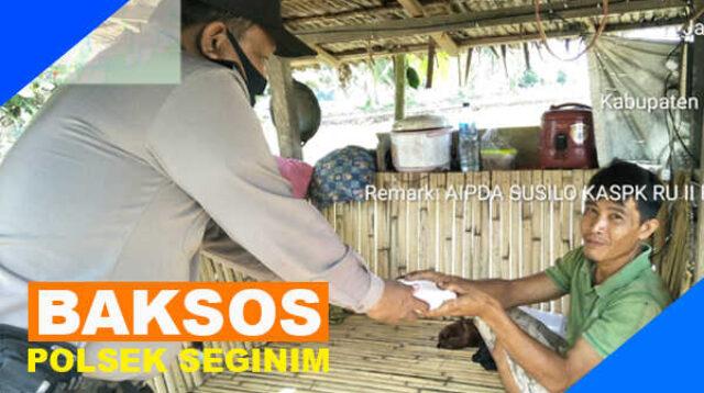 Aipda Susilo menyerahkan bantuan makan siang kepada salah satu warga Seginim