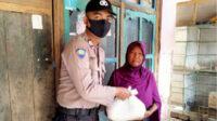 Brigpol Irfan menyerahkan bantuan sembako kepada salah satu warga