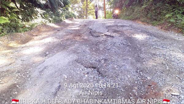 Bhabinkamtibmas Bripka Heri Defriady di lokasi jalan berlubang, Minggu sore