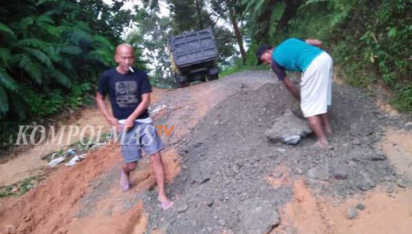 Edison alias Gundul (kiri) tertangkap basah menimbun lubang jalan menuju Desa Pino Baru dan Suka Maju, Sabtu lalu