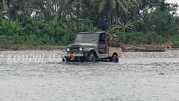 Seorang petani mengangkut TBS sawit tengah berusaha menerabas Sungai Air Nipis, di Desa Darat Sawah