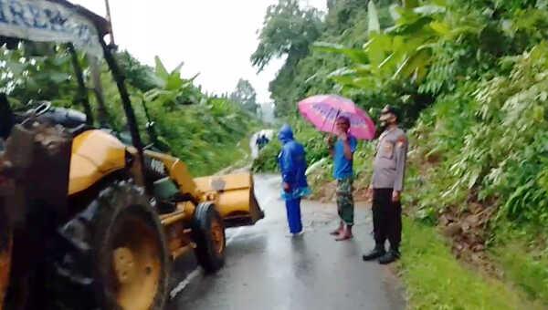 Petugas bersama masyarakat dibantu satu unit loader masih berupaya menyingkirkan material longsor dari jalan raya