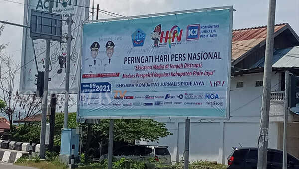 Selembar spanduk berisi ajakan partisipasi mengikuti rangkaian kegiatan memperingati HPN ke-75, terpajang megah di pinggir jalan protokol ibukota Kabupaten Pidie Jaya